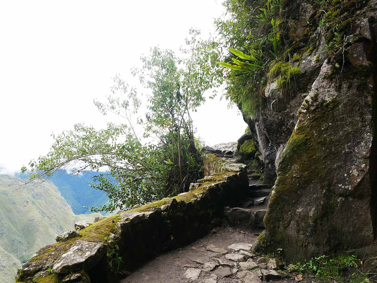 A narrow, winding stone path leads to the Inca Bridge along the side of a mountain.
