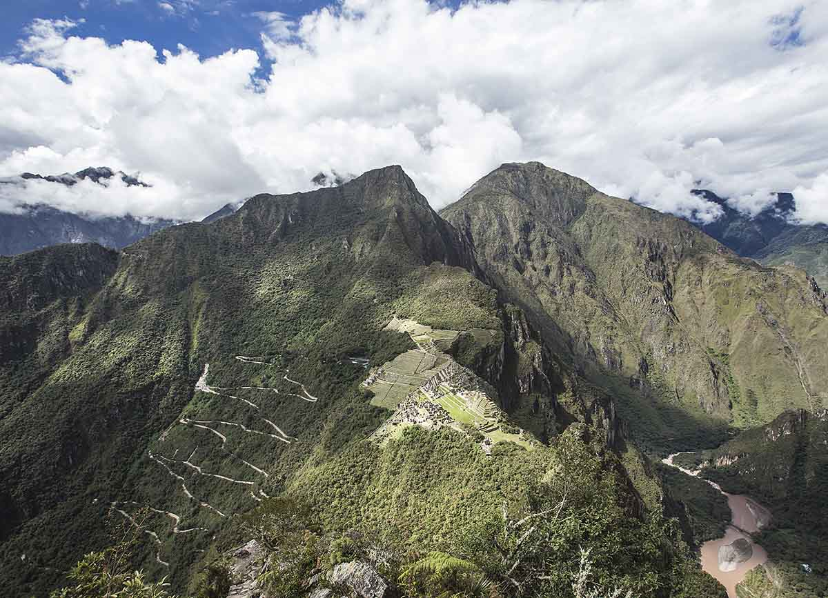 An aerial view of the Machu Picchu citadel from the Huayna Picchu peak. Blue skies, clouds, and lush green mountains surround the stone ruins.