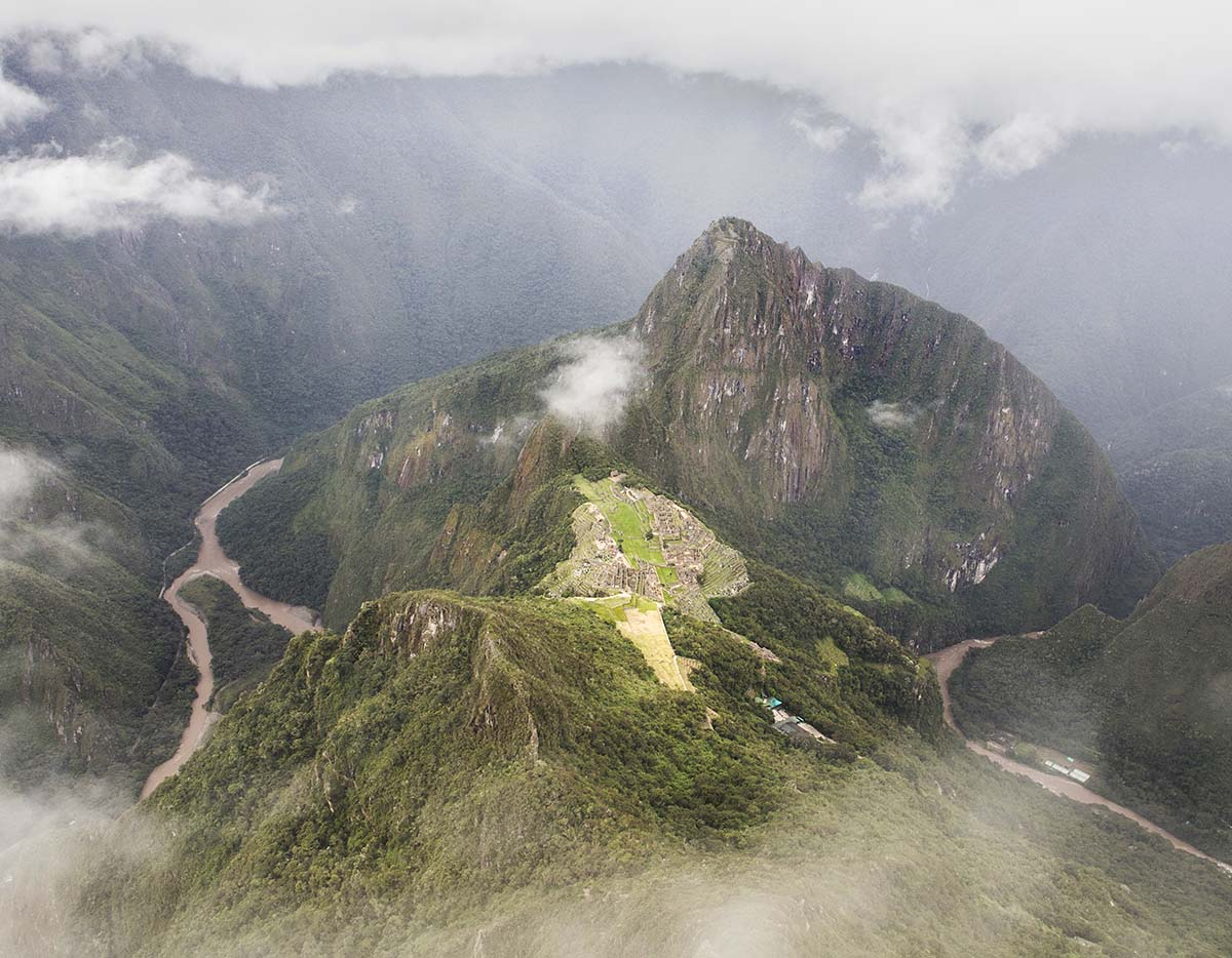 Machu Picchu ruins and Huayna Picchu peak. Clouds pour in from all angles, blurring the view.