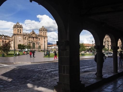 The main plaza in Cusco as seen from behind a few stone pillars.
