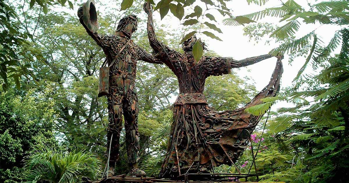Two human statues made of metal pieces dancing cumbia together with green trees and plants surrounding them.