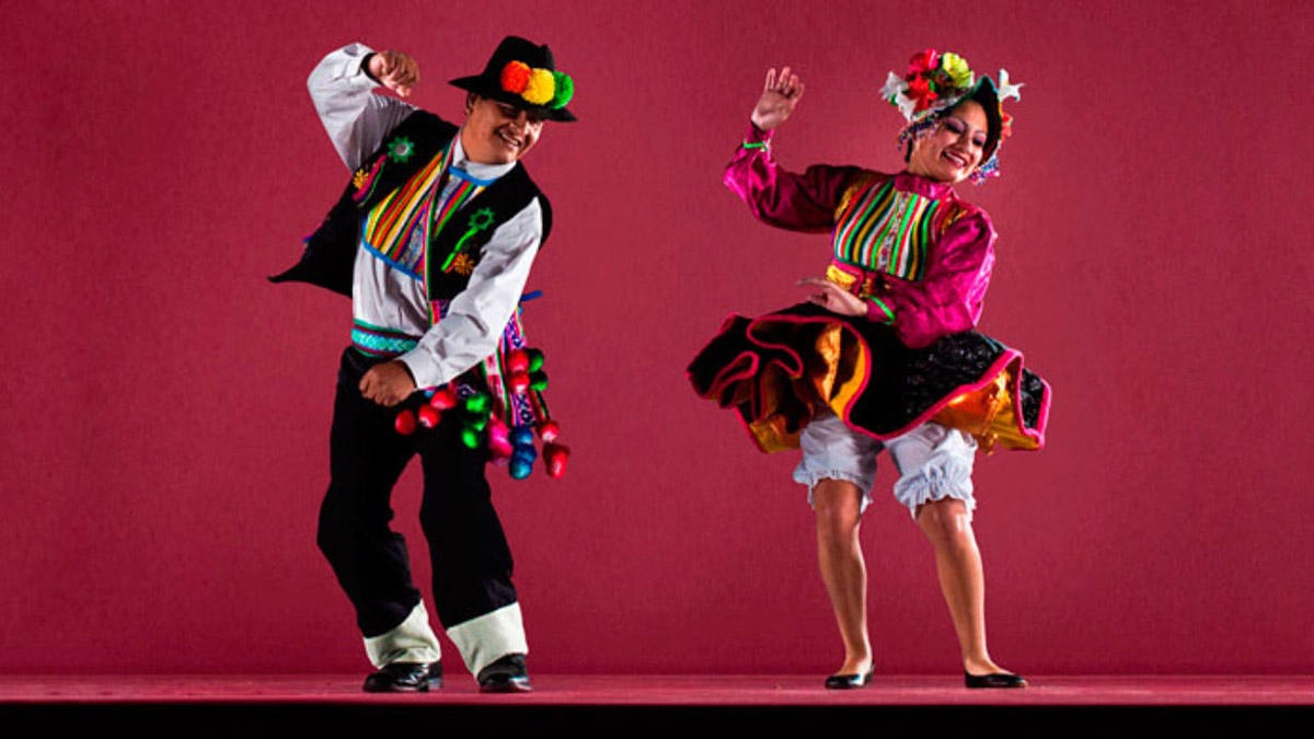 Two people dancing huayno in colorful attire with pink background.