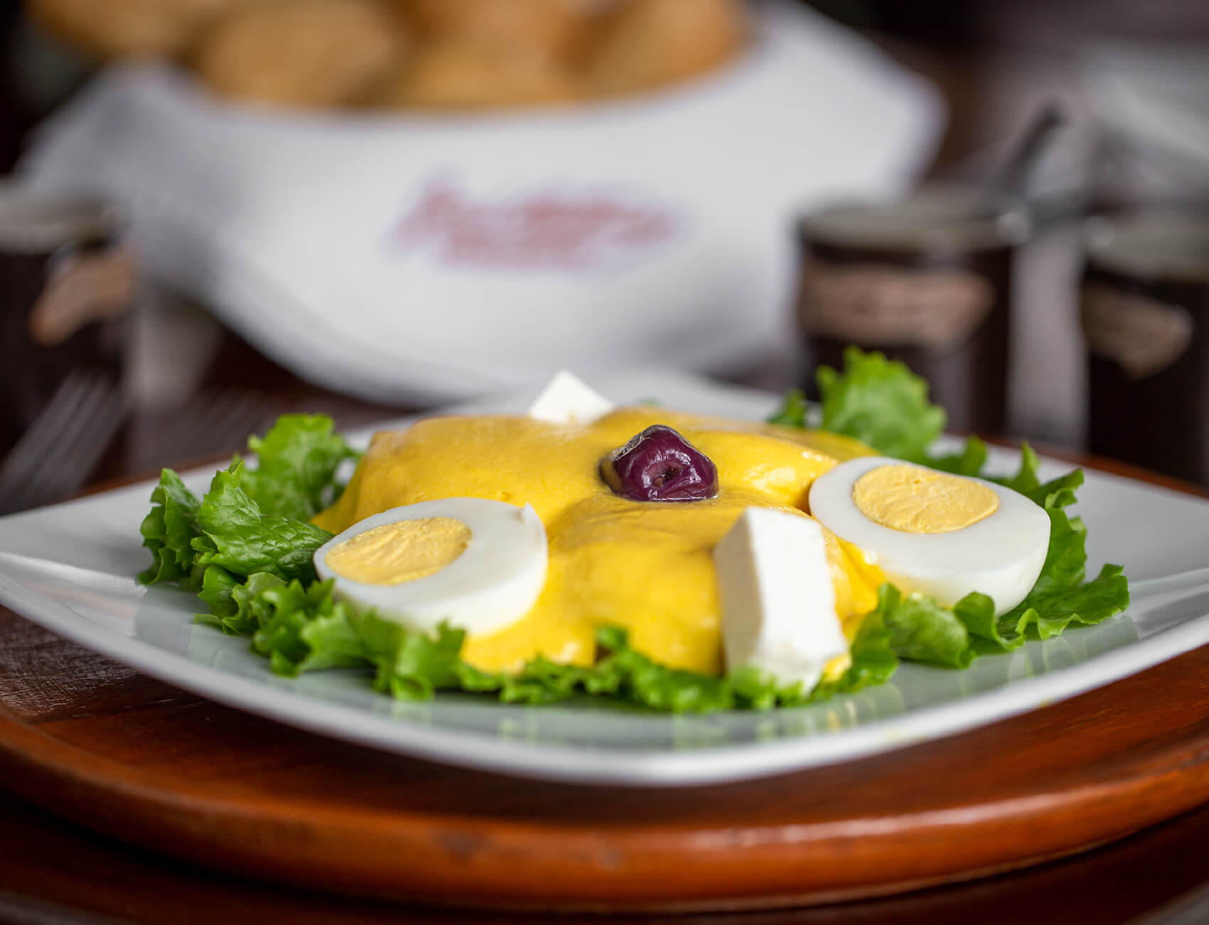 Photo of a plate of papa a la huacaina, garnished with lettuce, sliced hardboiled egg, and an olive.