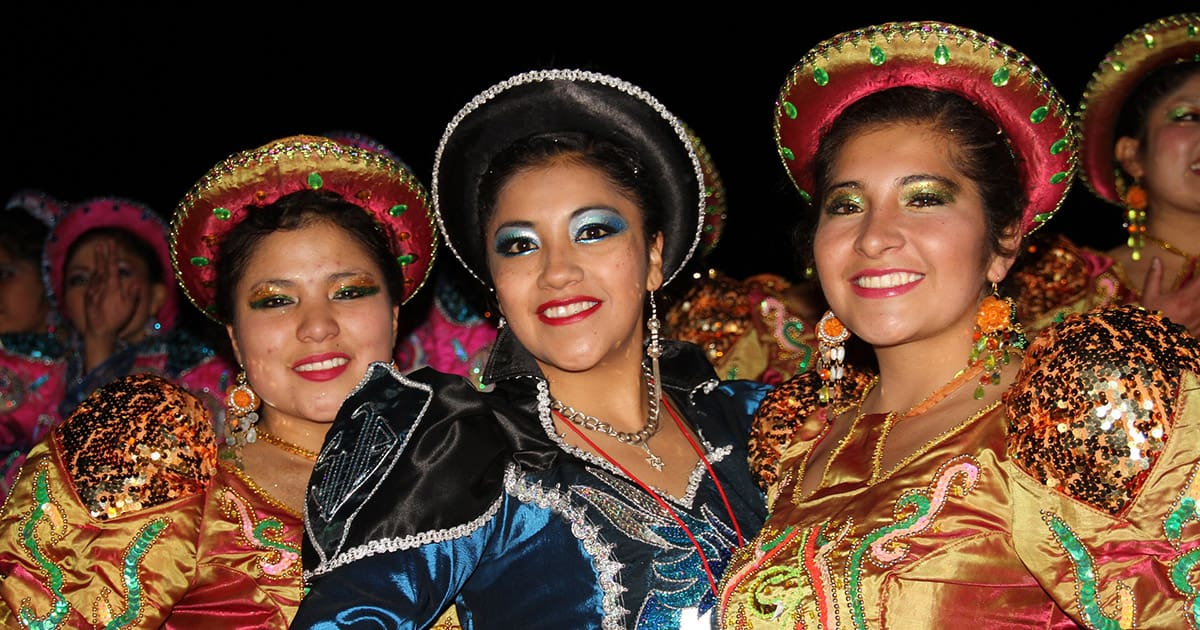 Three women in colorful traditional clothing at the Virgen de la Candelaria Festival in Puno.