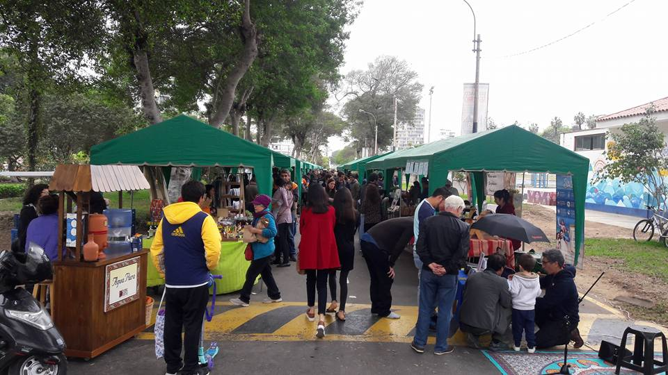Wide shot of the Barranco farmers market, consisting of tables lining the streets with green awnings.