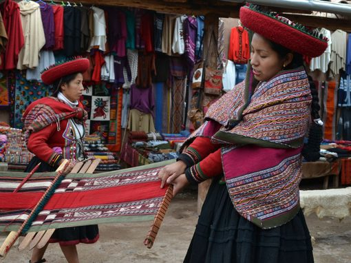 A native Quechua woman showing off a traditional Peruvian textile in the Sacred Valley.