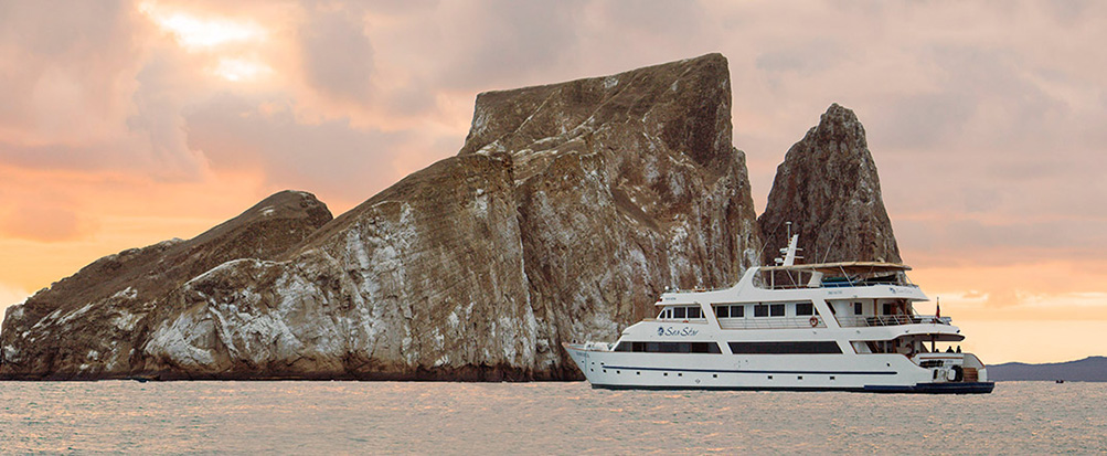 The Sea Star cruise ship sailing in front of Kicker Rock, a jagged rock formation, at sunset.