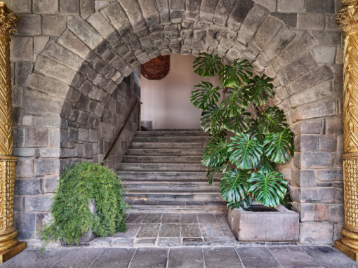 A stone archway to a stone staircase with plants on either side at Palacio del Inka hotel.