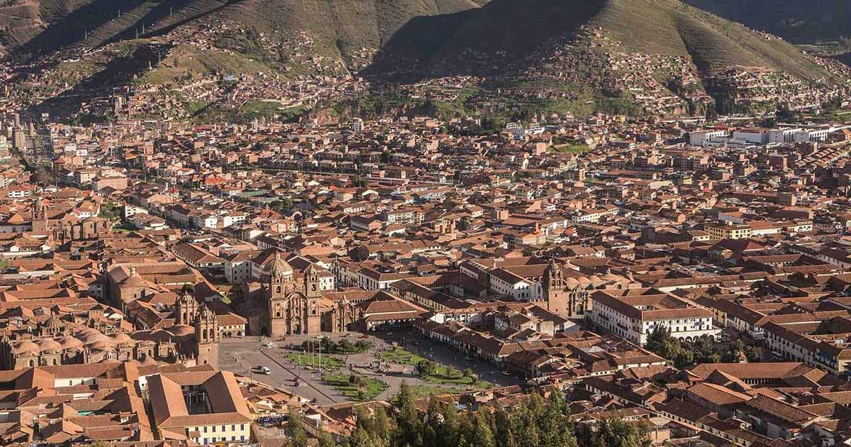 Looking down on Cusco plaza and surrounding areas. Brown tiled rooftops and mountains behind.