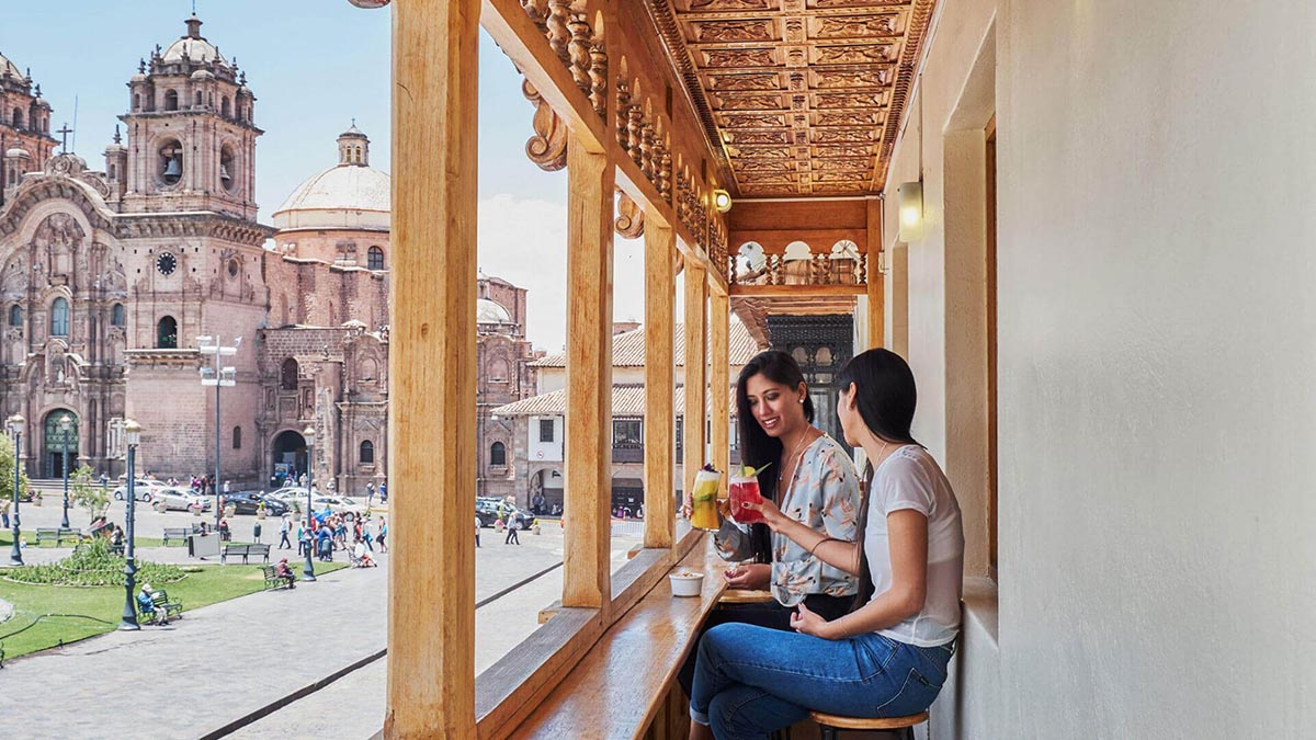 Two women toast on a wood balcony overlooking the Cusco plaza.