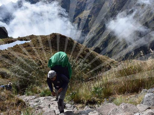 Inca Trail porter wearing a backpack and walking up stone steps