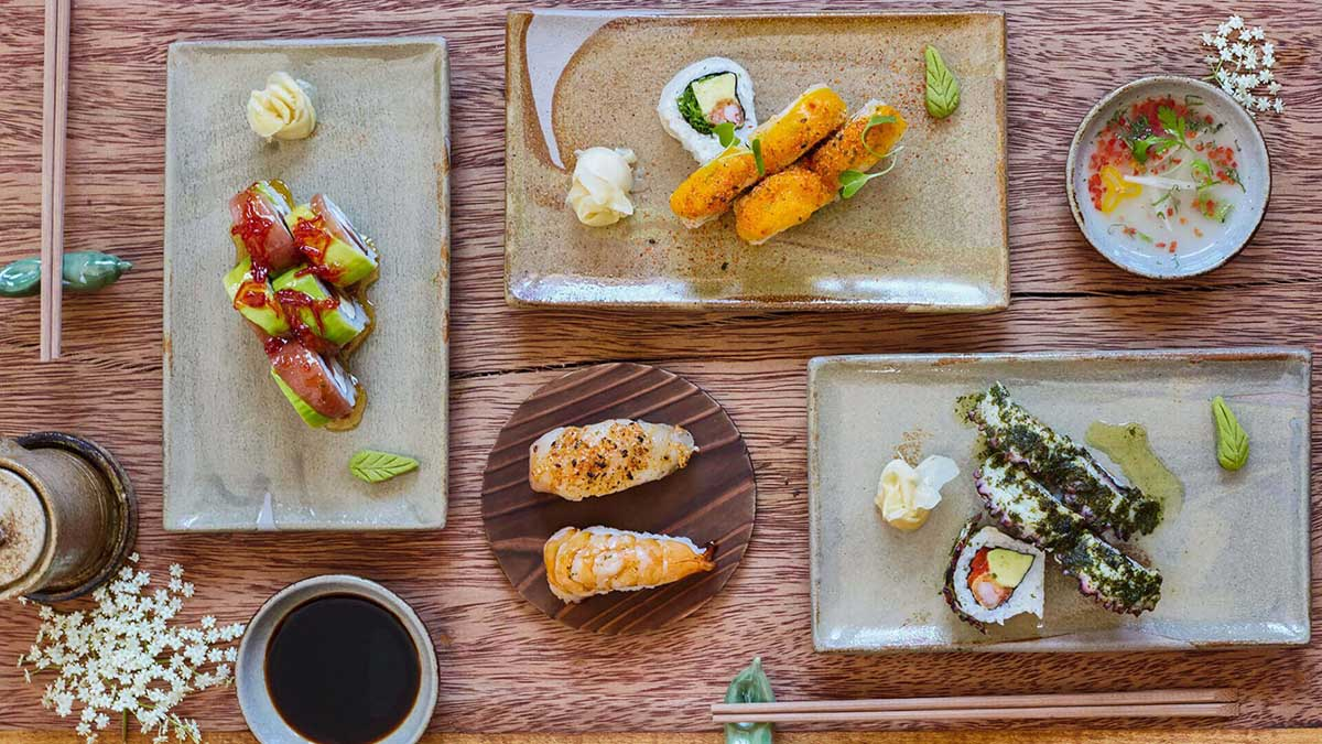 Close up of several sushi dishes on ceramic plates.
