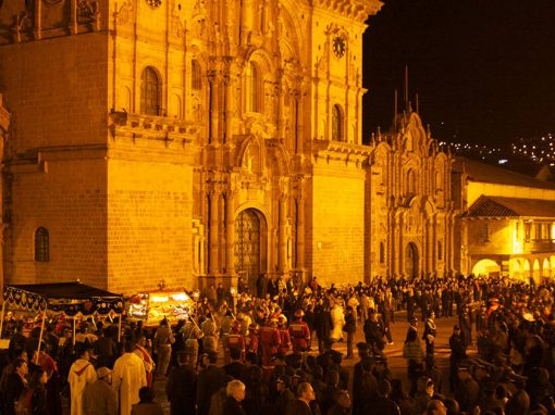 Crowds of people gathered in front of the Cusco Cathedral at night for an Easter procession.