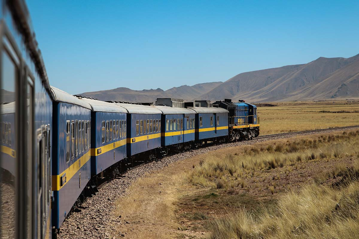 View of the Titicaca Train passing through the highlands with mountains and blue sky in background