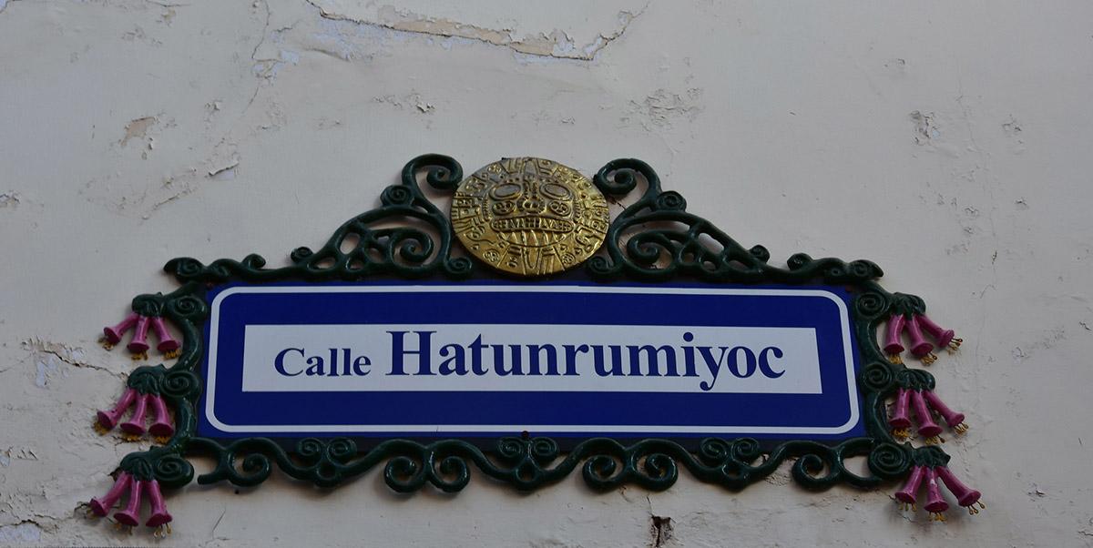 Decorative street sign of Calle Hatunrymiyoc on white wall.