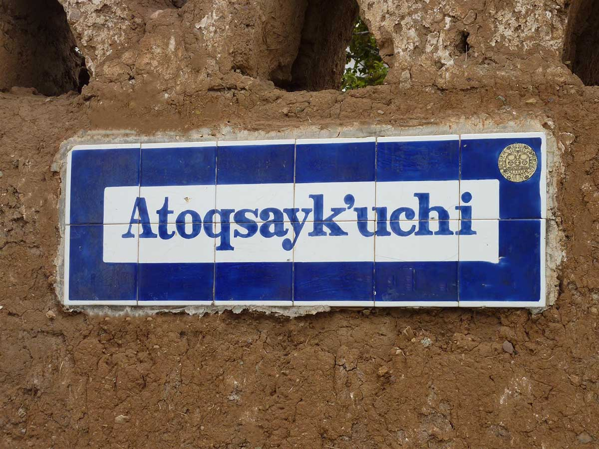 """White street sign with blue border that says """"Atoqsayk'uchi"""" on brown wall in Cusco."""