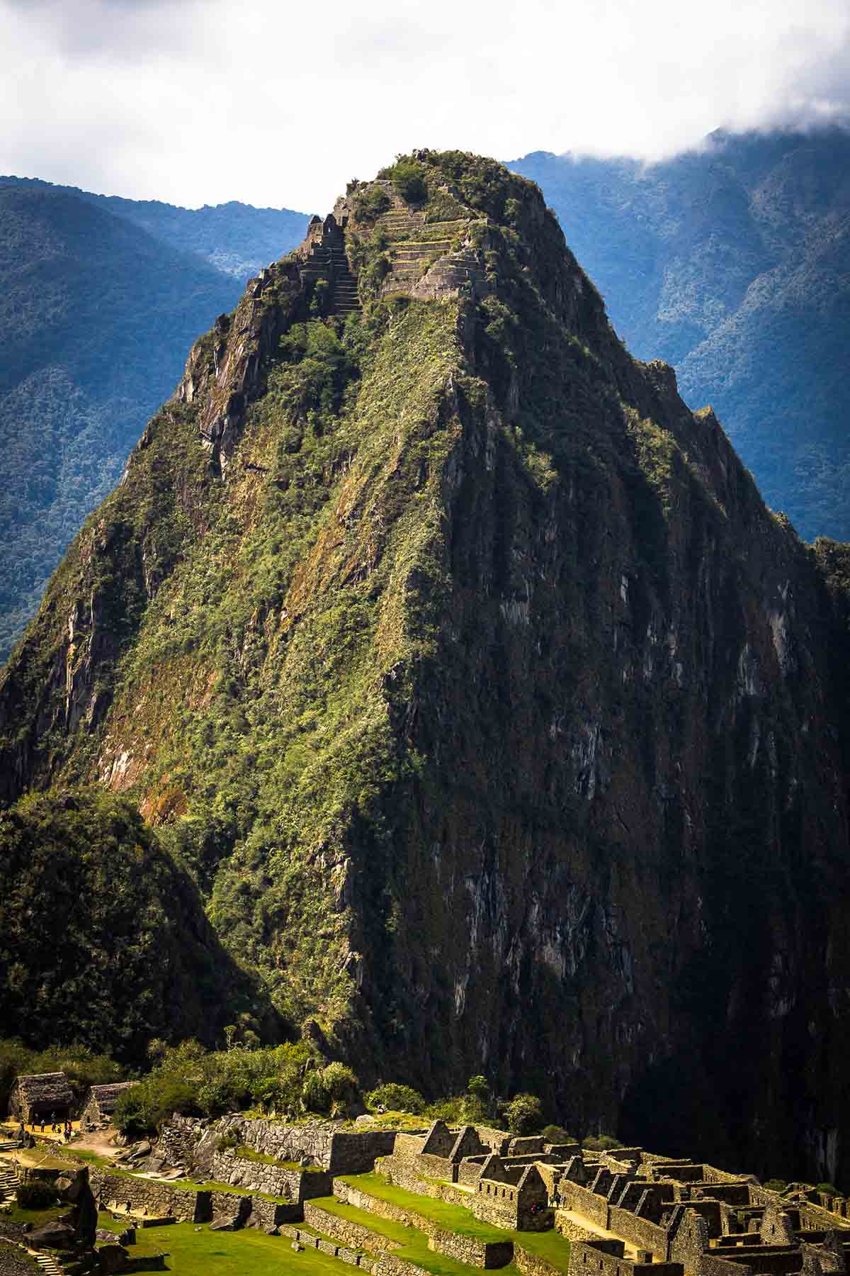 Huayna Picchu looms over the Machu Picchu ruins with the Moon Temple visible at the top.