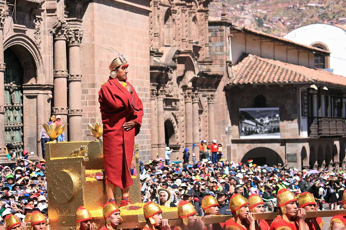 Man standing on a raised, gold throne for the Inti Raymi celebration. Spectators and Cusco Cathedral in background.