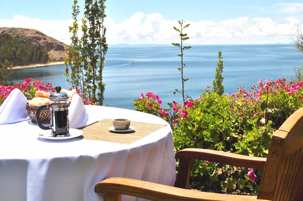 Breakfast table with coffee and bread basket at Isla Suasi hotel overlooking Lake Titicaca.