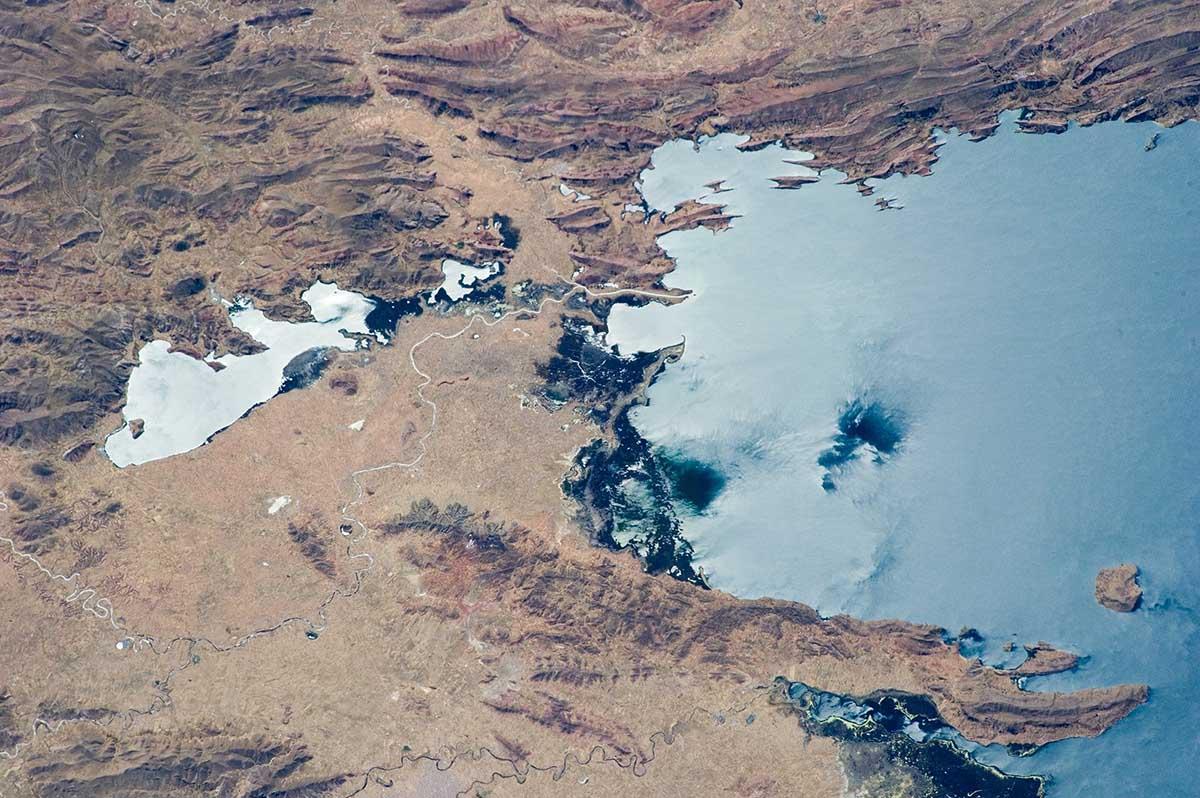 Aerial view of rough, brown terrain meeting blue Lake Titicaca.
