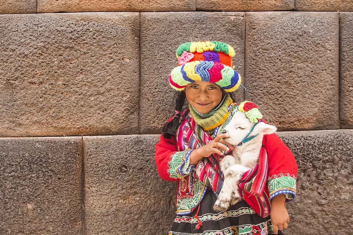 Young Quechua girl in multicolored traditional dress holding a baby lamb.