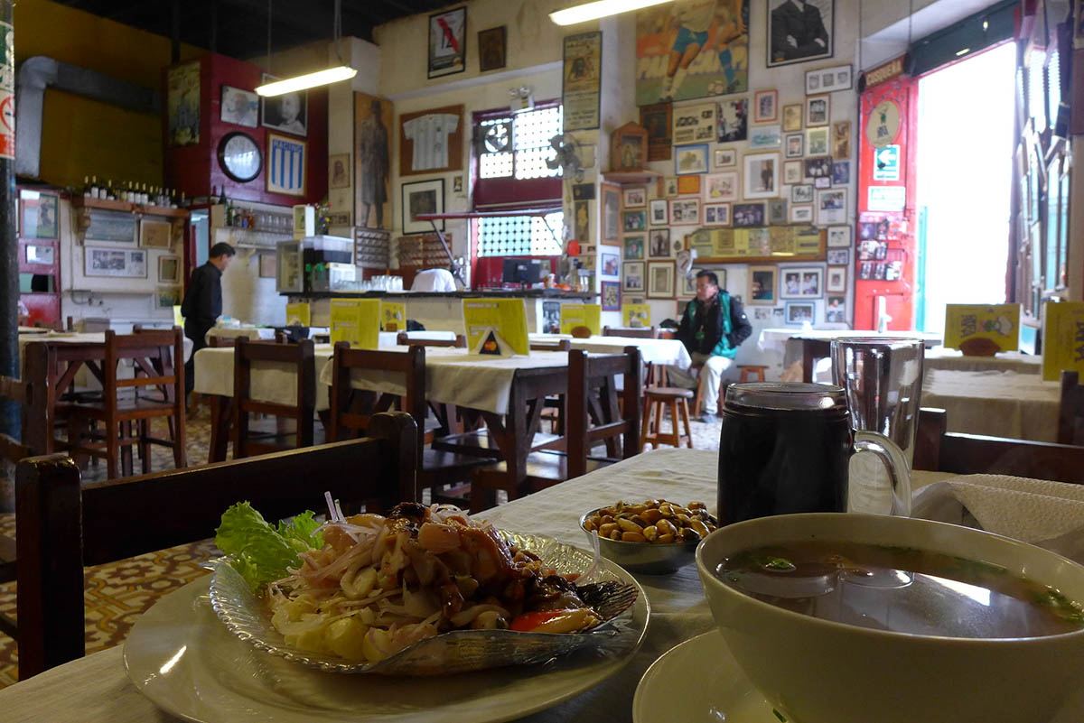 A bowl of soup and plate of ceviche on a white clothed table with a wall covered by framed photos in the background.