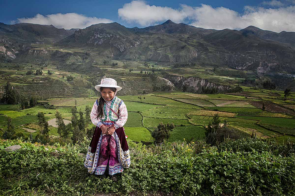 Young girl dressed in colorful traditional clothing with green terraces in Colca Canyon behind her.