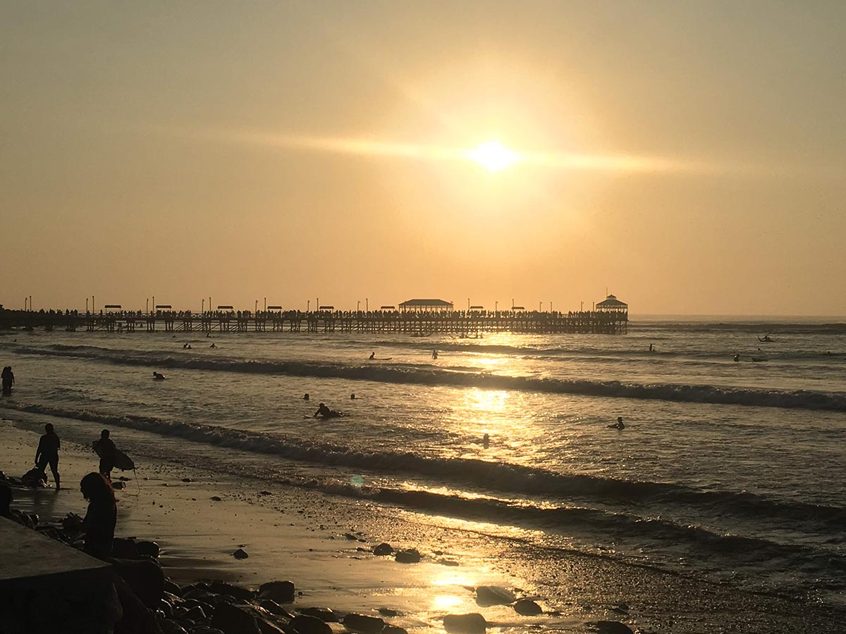Sunset over a century-old pier in Huanchaco, Peru with people swimming in the low surf.