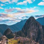 Machu Picchu archeological site with mountains in the background and colorful sky