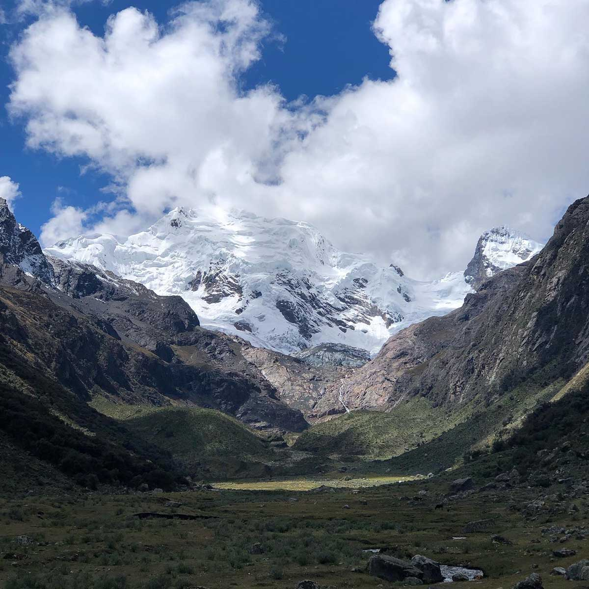 Clouds partially cover snowcapped mountains in huascaran national park, Peru.