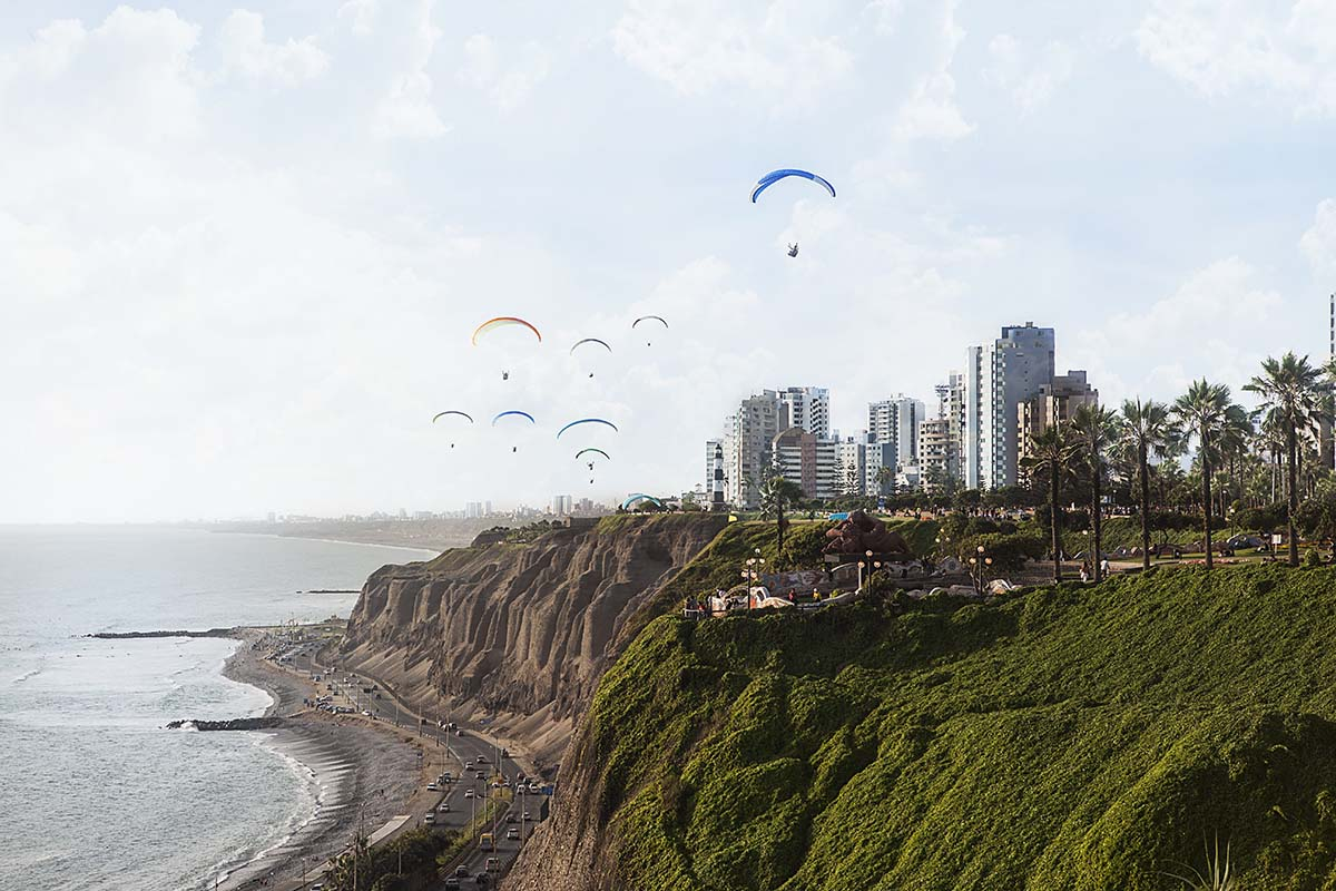 Paragliders in Lima soar over green cliffs, with views of the ocean and the city skyline