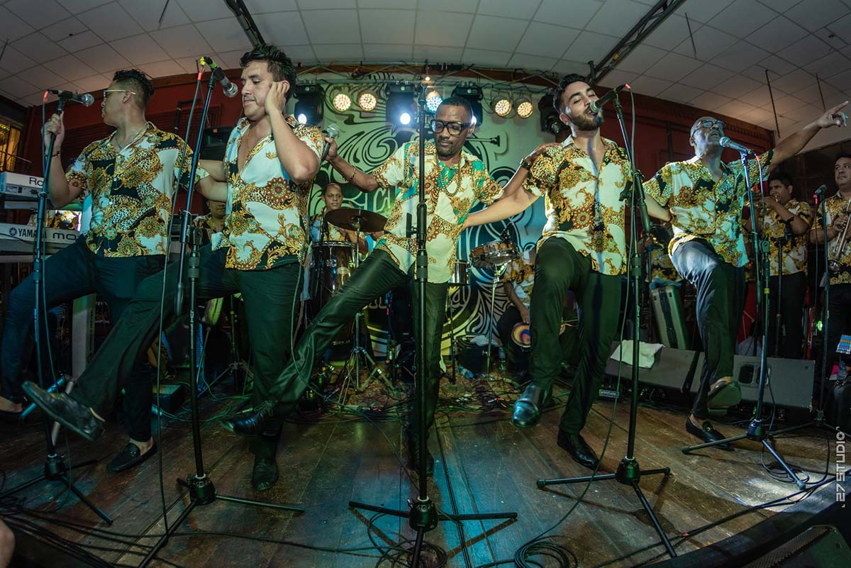 Five men in matching outfits sing and dance on a small stage at Sargento Pimienta in Lima