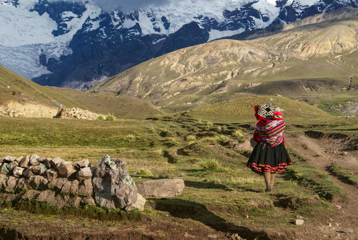 Woman in traditional Andean attire walking the in the Andes Mountains