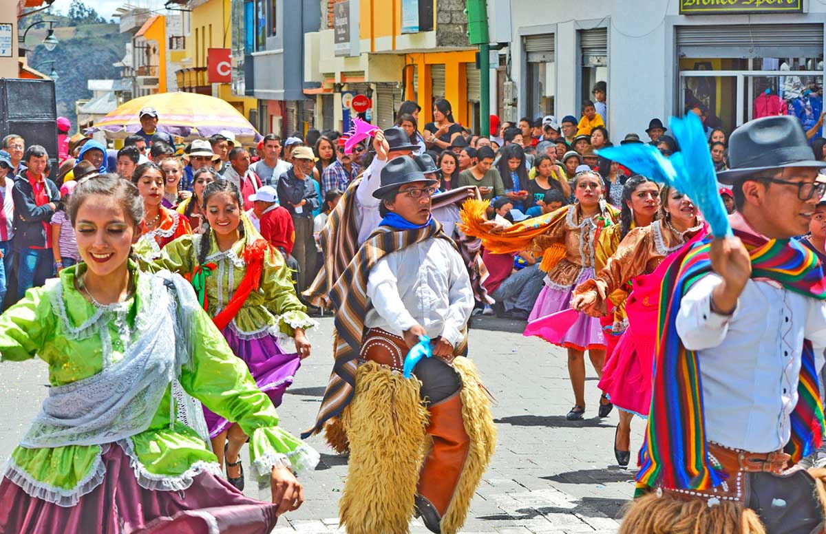 Group of men and women in traditional attire attending Carnival in Ecuador.
