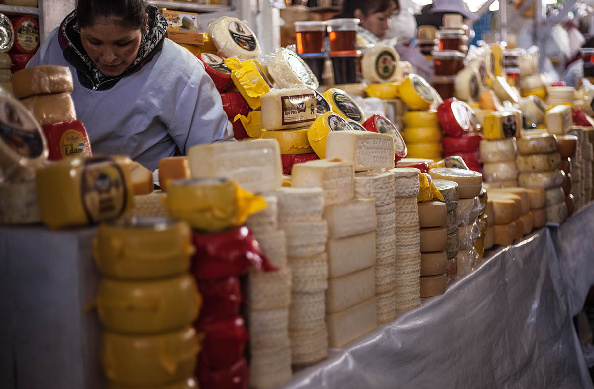 Ladies sell stacks of Andean cheese at the San Pedro Market in Cusco.