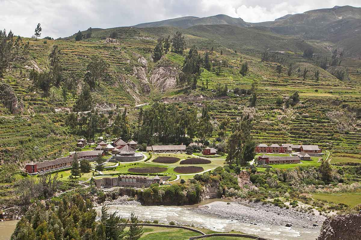 Looking down over the riverfront property of Colca Lodge in the green valley surrounded by terraces.