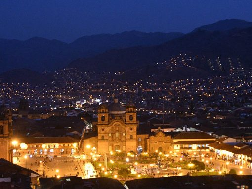 A brightly-lit view of Cusco city's main Plaza de Armas at night.