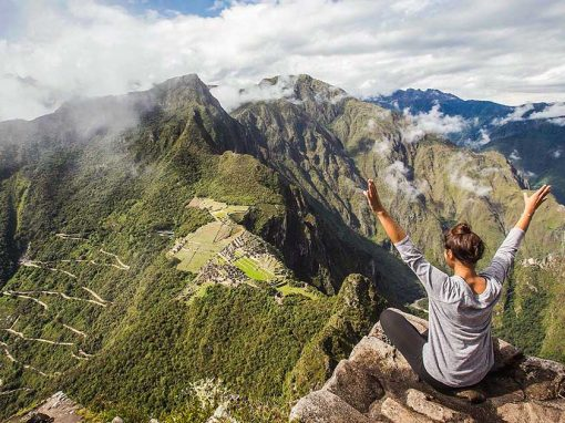 A girl sits atop the Huayna Picchu viewpoint with arms outstretched, while she looks at the ruins below.