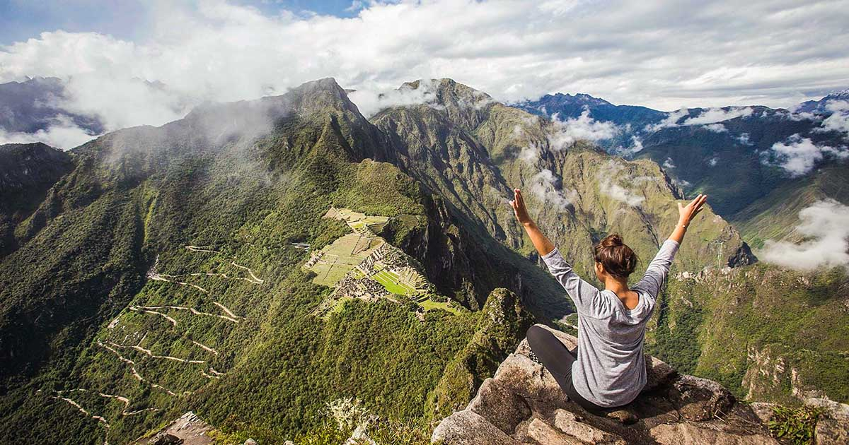 A visitor at the Huayna Picchu viewpoint with arms outstretched, looking at the ruins below.