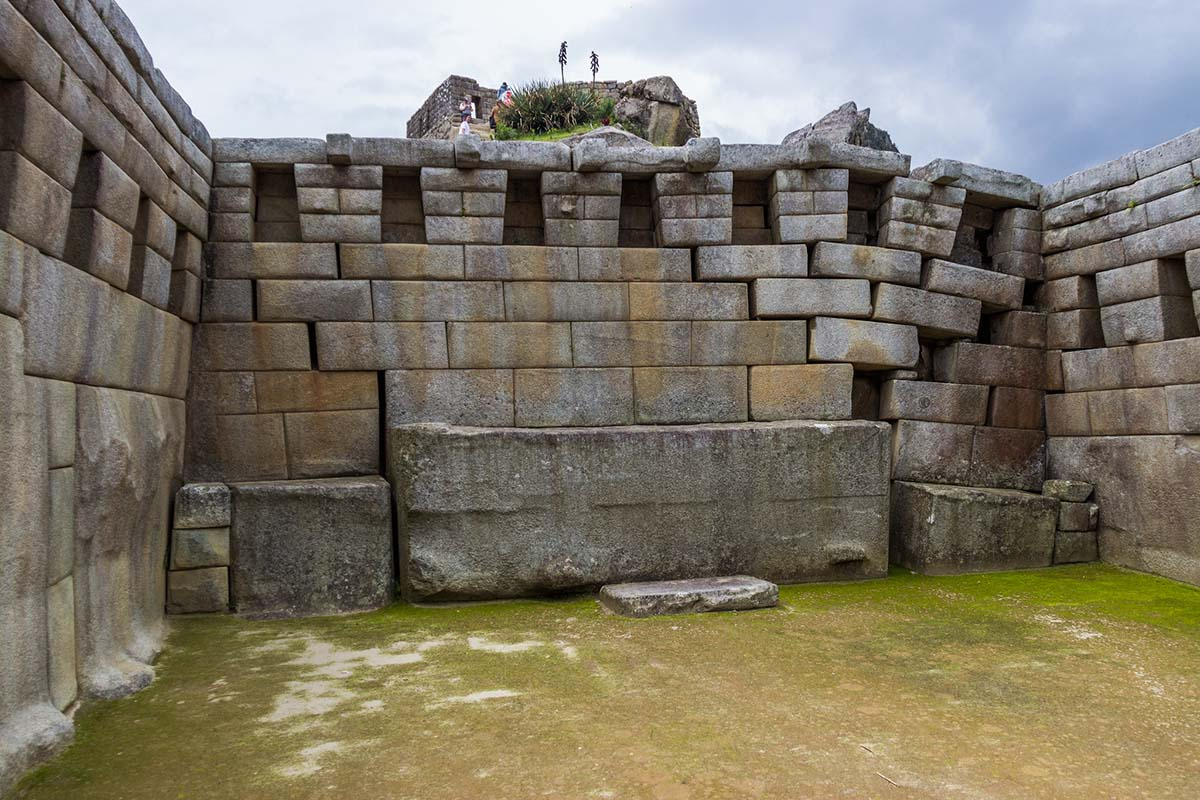 A view of Inca stonework in Machu Picchu on a cloudy day.