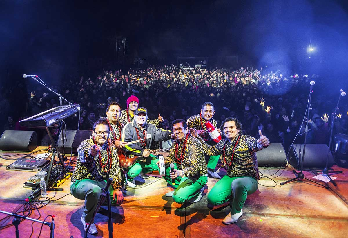 Seven performers of Los Mirlos smiling on stage with a live audience behind.