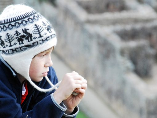 A child in a winter hat looks over the ruins of Machu Picchu.