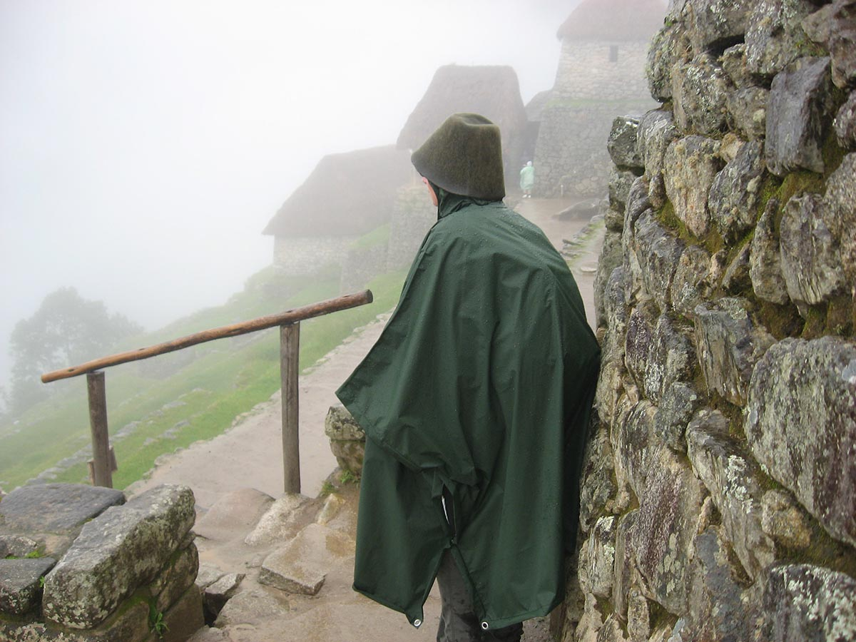 A visitor to Machu Picchu in dark green poncho and bucket hat standing next to an Incan wall.