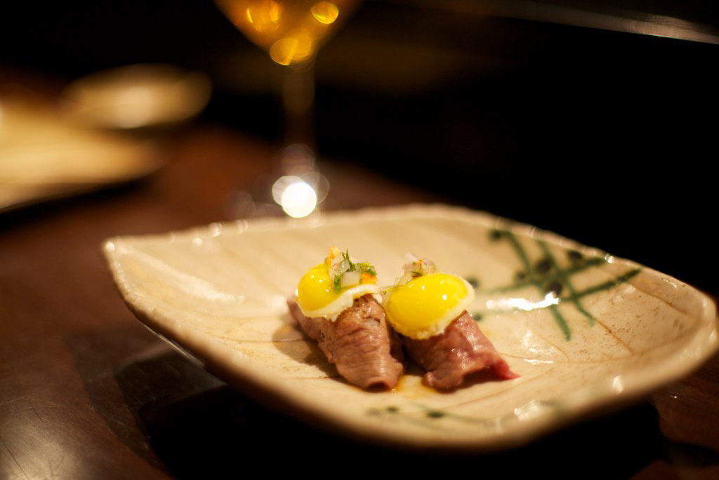 A dish from Maido. Two pieces of cooked red meat garnished with yellow egg yolks on a ceramic plate.