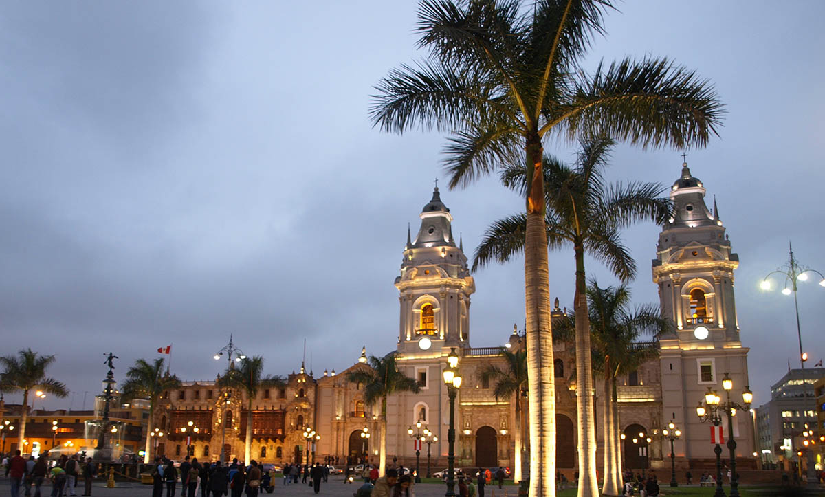 The Lima Cathedral's façade illuminated in yellow light in the historic downtown center of Lima