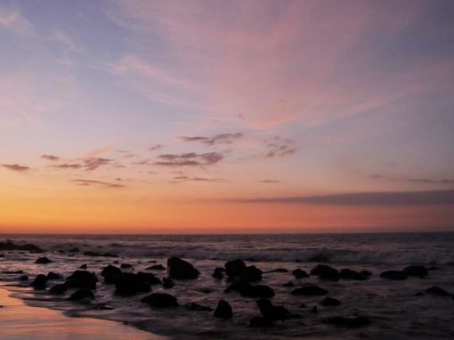 Sunset over the Pacific ocean dotted with lava rocks from Mancora beach in Northern Peru.