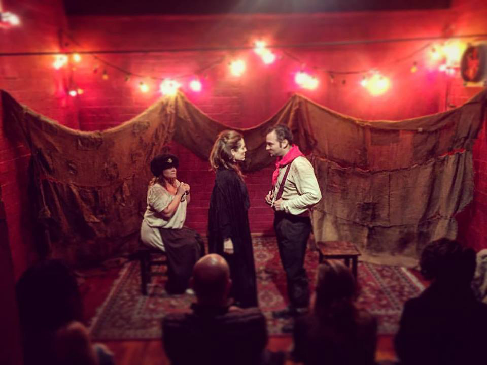 A play at the microteatro in Lima with a man and woman standing and another actress sitting behind.