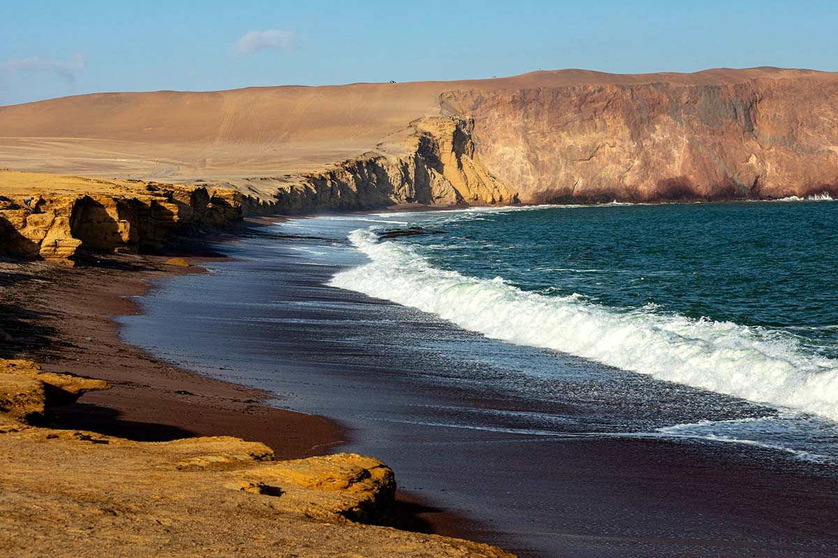 Yellow desert meets foaming blue ocean waves at Playa Roja in the Paracas National Reserve.