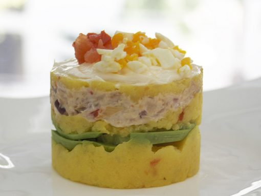 Causa rellena with avocado and creamy chicken topped with chopped egg and tomato.