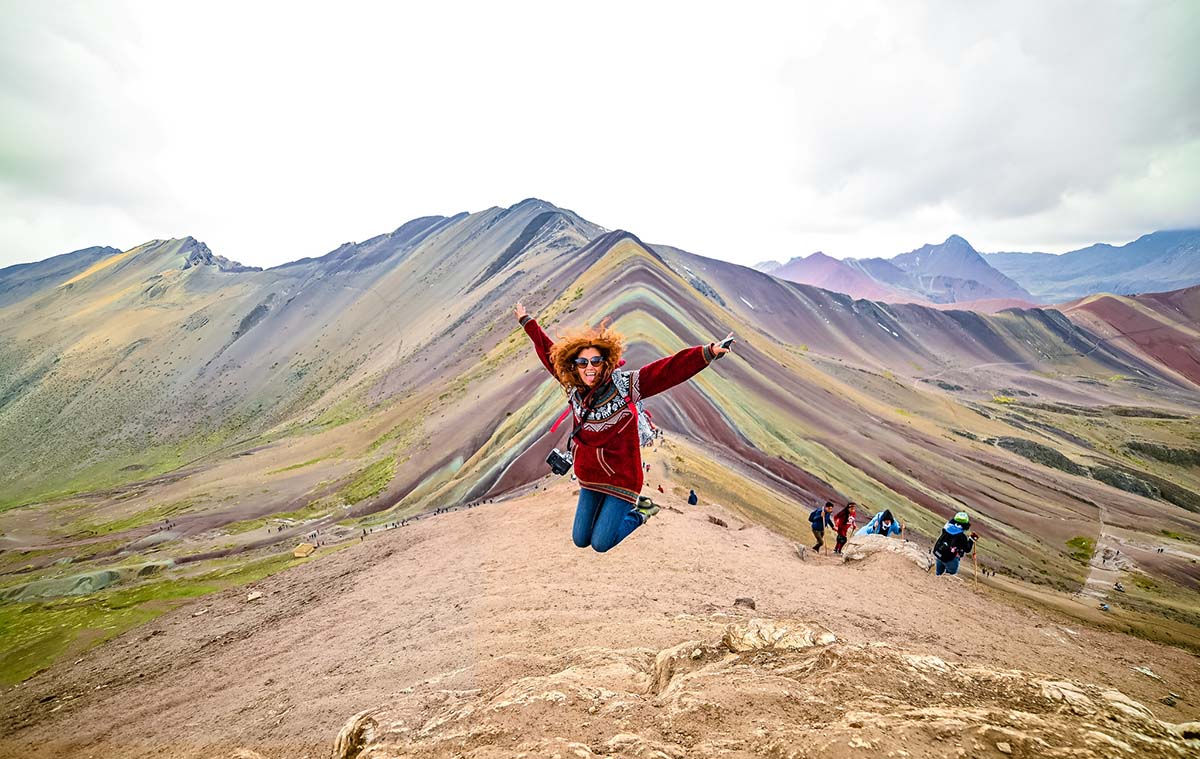 A woman with bright red hair jumps for a photo in front of the Rainbow Mountain in Peru.